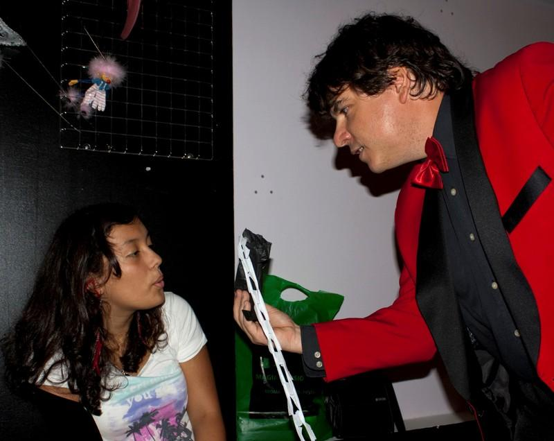 Magician Olivier OK MAGICS interacting with spectator during close-up show in La Porra Pamplona Spain 2011