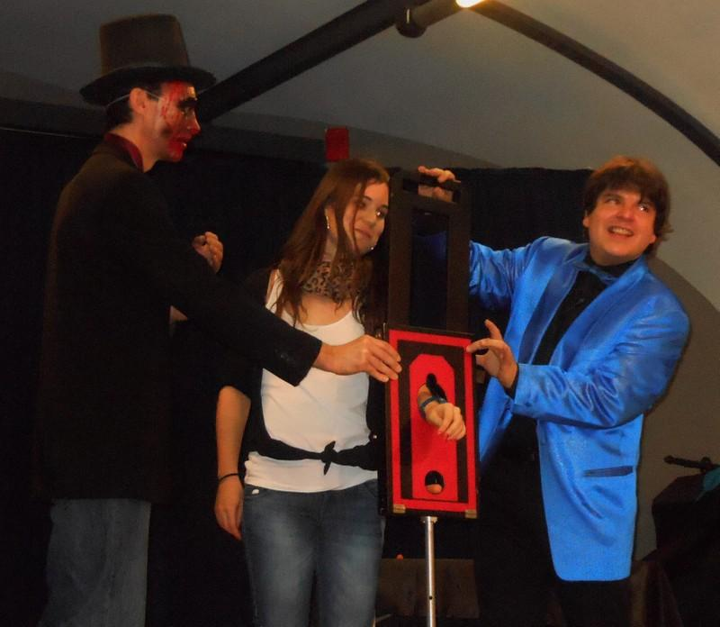Magician Olivier OK MAGICS performing arm guillotine with spectator Halloween Tour 2013
